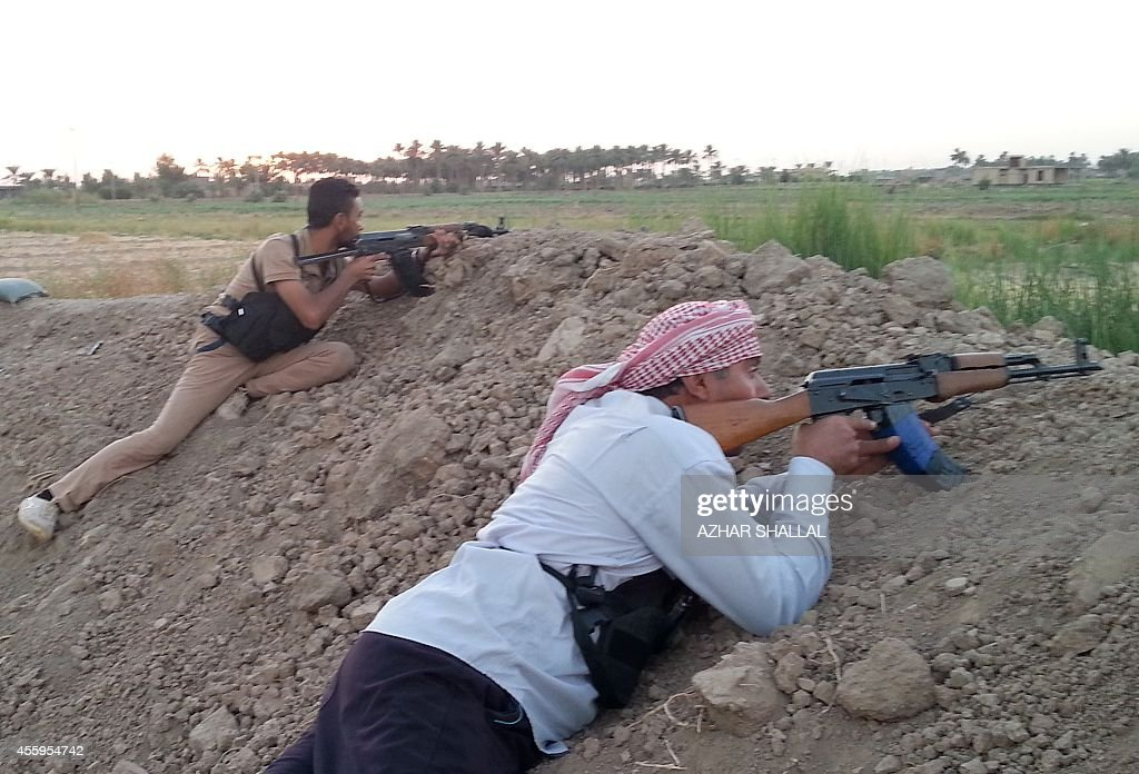 In a picture taken with a smartphone on September 22 Iraqi tribal fighters backing government forces take a position behind a berm as they fire at...