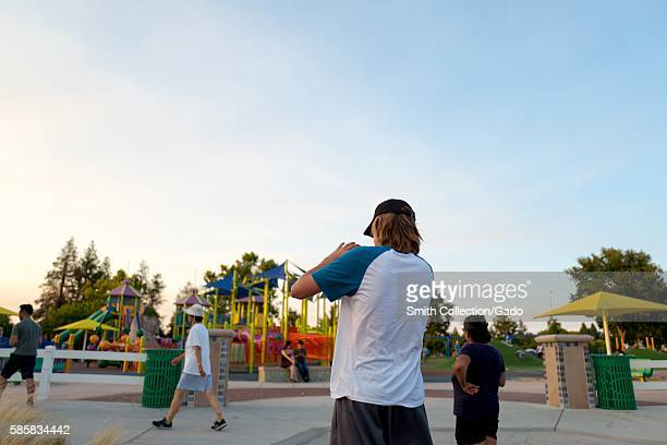 In a public park in the San Francisco Bay Area a teenager is viewed from behind in silhouette as he swipes on his smartphone while playing the...