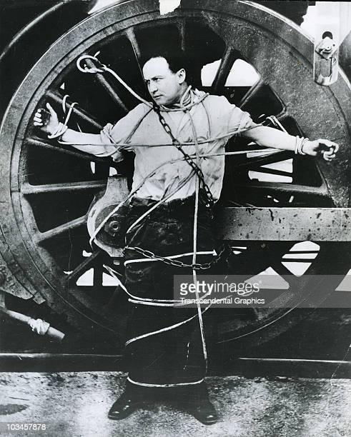 harry houdini strapped to a locomotive wheel