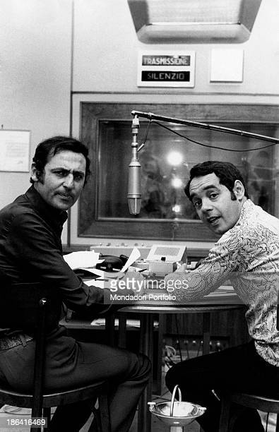 In a radio station the broadcast presenters Renzo Arbore and Gianni Boncompagni turn toward the photographer in the same year the two artists began...