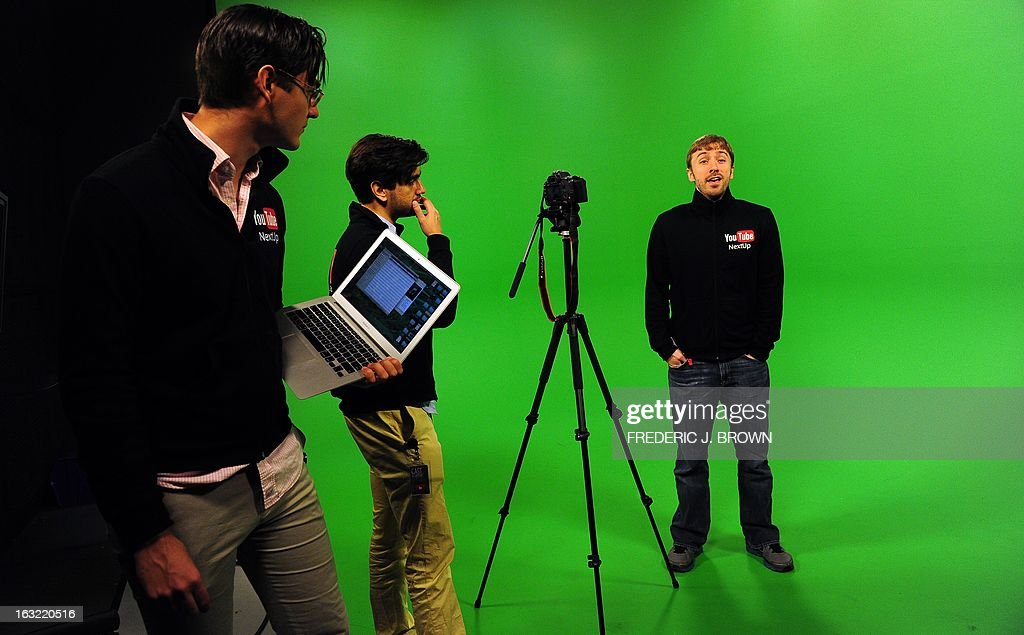 In a recycled hangar in Los Angeles, California on February 8, 2013, videobloggers from across the country learn how to use production equipment in facilities worthy of Tinseltown at YouTube Space LA, a free facility created by Google to pamper its hardcore fans. Seen here in the middle of a production are Peter Hollens (R) performing for the camera as Antonius Nazareth (L) and Vijay Nazareth (C) watch. AFP PHOTO/Frederic J. BROWN