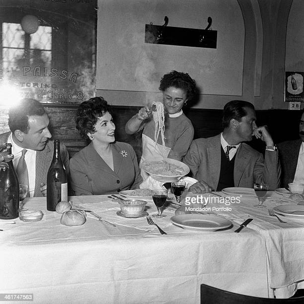 In a restaurant a waitress serving a dish of spaghetti to Italian actress Gina Lollobrigida and her husband Slovenian doctor Milko Skofic The actress...