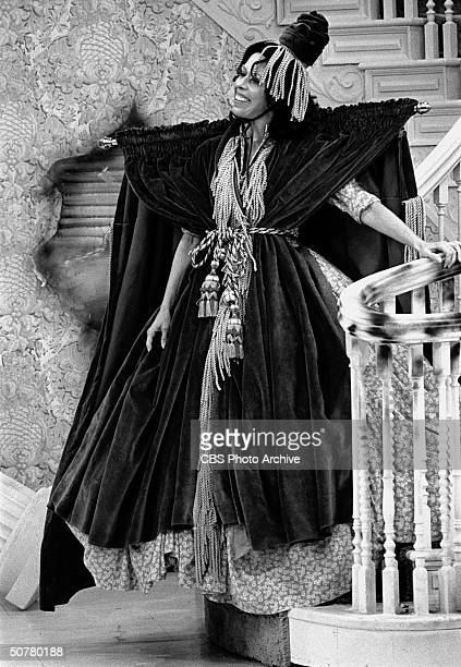 In a scene from 'The Carol Burnett Show' American comedienne and actress Carol Burnett descends a staircase dressed in dress made from a window...
