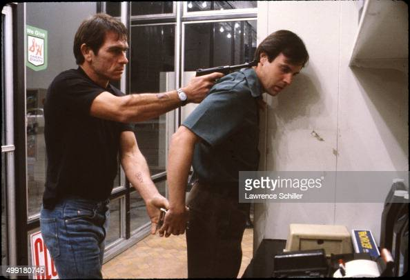 In a scene from the madefortelevision movie 'The Executioner's Song' American actor Tommy Lee Jones holds a gun to the head of actor Bruce Newbold...