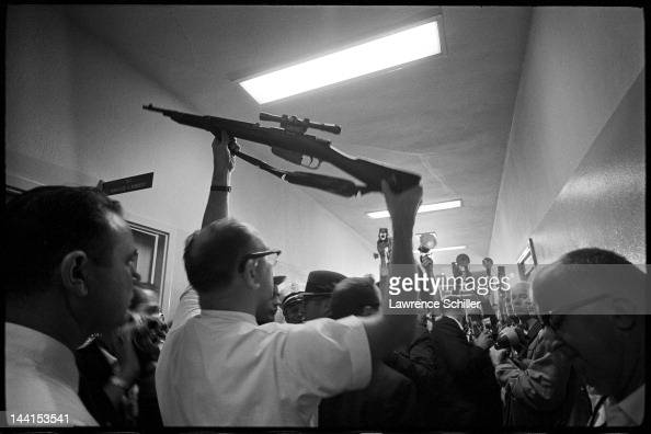 In a second floor hallway in the Dallas Police Department building crowded with members of the press an unidentified man holds up the rifle alleged...