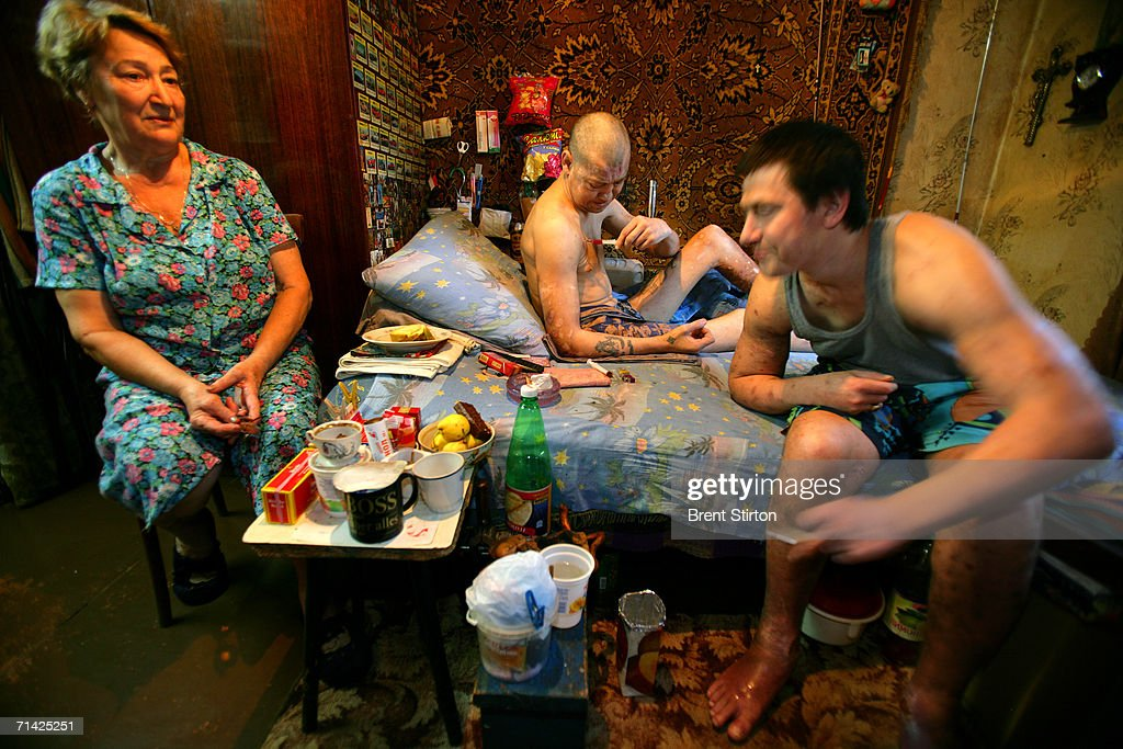In a small apartment two brothers shoot up drugs while their mother looks on helpless in her own home on August 12, 2005 in Poltava, Ukraine. Alla, left, is the mother of Dima, 39, middle, and Ruslan, 36, right. They have been addicts for over 20 years and in that time both sons have had daughters. Alla lost her husband 15 years ago and had to quit her job as a kindergarten teacher to look after her addict sons. Ruslan, the younger son, often berates her for being a bad mother as a means of controlling her and ensuring that she will continue to look after him and his brother. It is rumoured in the neighbourhood that the family deals in drugs so as the two brothers can maintain their addiction. Getty Images is partnering with the Global Business Coalition on HIV/AIDS ongoing projects.