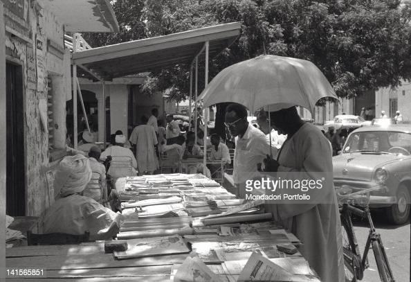 In a small Khartoum street full of parked cars two customers peer at the published items books secondhand magazines and newspapers on display at a...