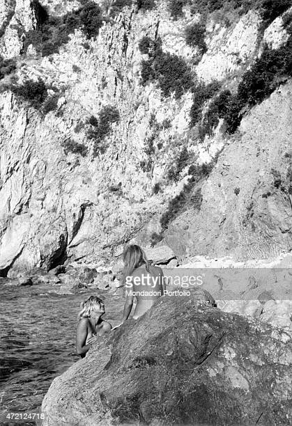 'In a solitary bay two young topless women bathe and sunbathe on the cliffs joking and talking together Capri Italy July 1960 '