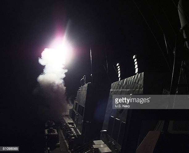 In A Split Second Flash Of Fire And Smoke A 'Tomahawk' Cruise Missile Starts Its Launch From The Forward Vertical Launch Missile Deck On Board USS...