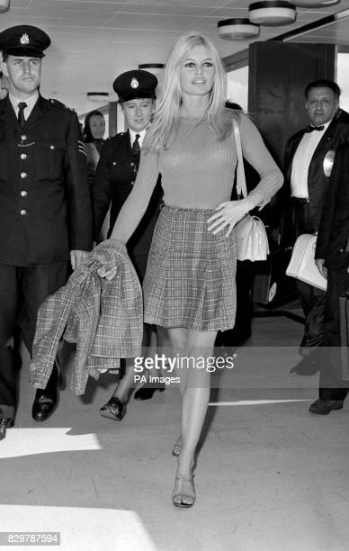 In a tartan nearlymini skirt and carrying a matching jacket French actress Brigitte Bardot arrives at London Airport to film the AngloFrench 'Two...