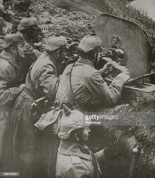 In a trench a German machine gun crew load and aim their weapon behind a metal shield 1910s