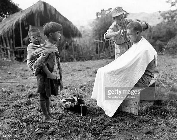 In a village in Burma a girl with a baby on her back watches a Chinese soldier cutting the hair of a American soldier from the 112th Regiment of the...