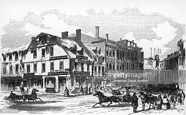 In an engraving from Ballou's Pictorial magazine titled 'Antique Building Corner of School and Washington Streets Boston' horse pull sleighs and...