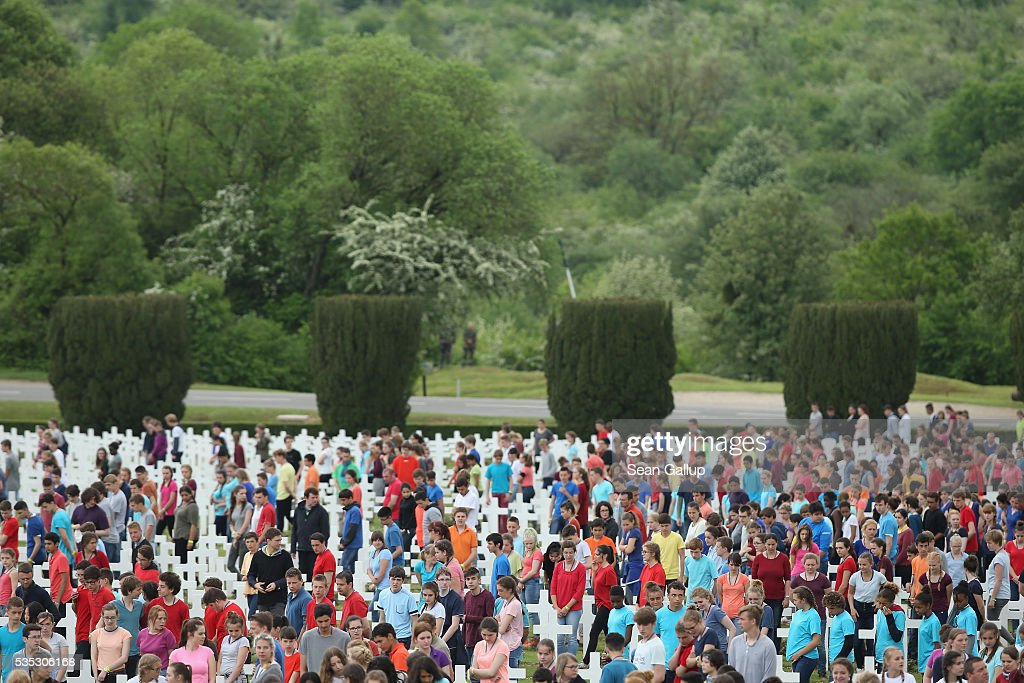 In an orchestrated event children walk among crosses at the Douaumont cemetery as th former battelfields of Verdun lie overgrown with trees behind during ceremonies to commemorate the 100th anniversary of the World War I Battle of Verdun on May 29, 2016 near Verdun, France. The 1916, 10-month battle pitted the French and German armies against one another in a grueling campaign of trench warfare and artillery bombardments that killed a total of approximately 300,000 soldiers. The events today coincide with the 50th anniversary of commemorations held at Verdun by then French President Charles de Gaulle and German Chancellor Konrad Adenauer that paved the way for a new era of peaceful, post-war Franco-German relations.