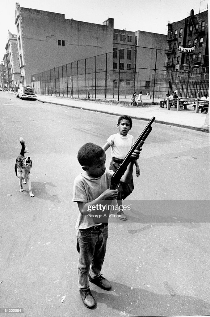 In an unidentified section of the Bronx, a young boy plays with a toy shotgun while another boy approaches him, 1969. A dog barks in the background.