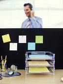 In and out filing tray with man wearing headset behind partition