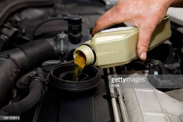 In auto repair shop...Car mechanic is changing engine oil