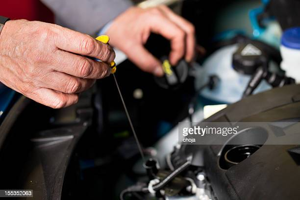 In auto repair shop...Car mechanic is checking motor oil