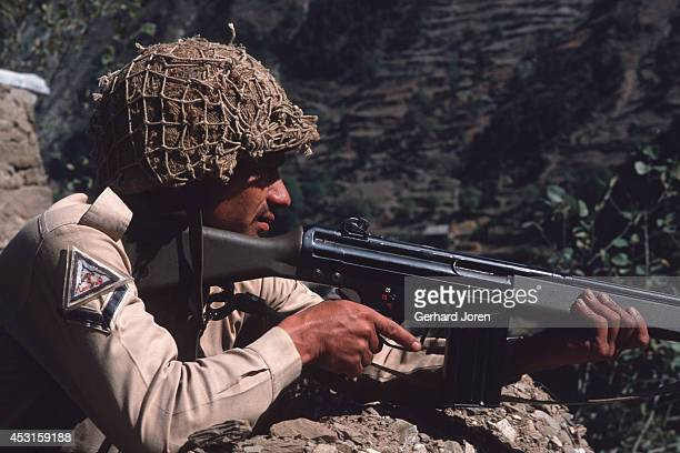 In Azad Kashmir a Pakistani soldier on guard with rifle looking out over the Indian side of Kashmir A river 100 meters below constitutes the border