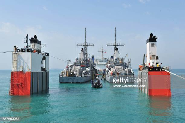 In calm turquoise waters two mine countermeasure ships USS Pioneer and USS Warrior prepare for transport behind merchant vessel Super Servant III...