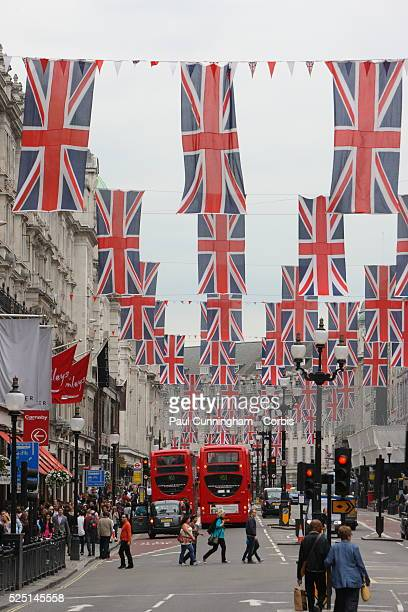 In celebration of the forthcoming Diamond Jubilee Union Jack flags and bunting flutter above the streets and shop windows display crowns and flag...