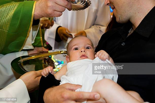 In church.Priest ist baptizing kleines baby.