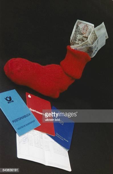 In einem Strumpf stecken drei Geldscheine darunter liegen ein Postsparbuch ein Sparkassenbuch und ein Sparbuch der Deutschen Bank auf einem...