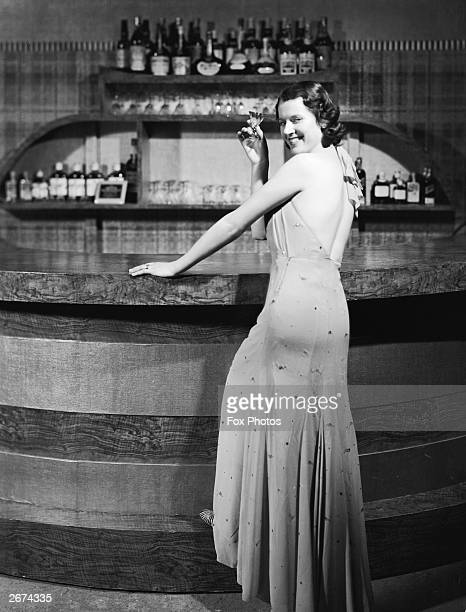 In evening dress Kay Streatfield drinks a cocktail at a bar