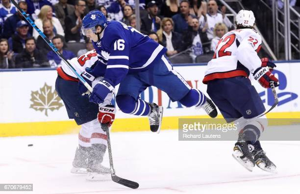TORONTO ON APRIL 19 In first period action Toronto Maple Leafs center Mitch Marner goes high over Washington Capitals center Jay Beagle on a drive to...