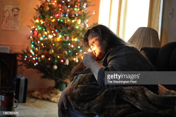 In front of a Christmas tree void of any presents Jenny Click fires up a cigarette butt from a tray full of them at her foreclosed home on December...