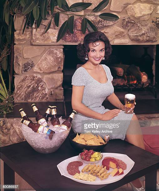 In front of a fireplace a woman smiles a glass of beer in her hand as she sits perched on the edge of a low table stocked with a bowl of iced beer...