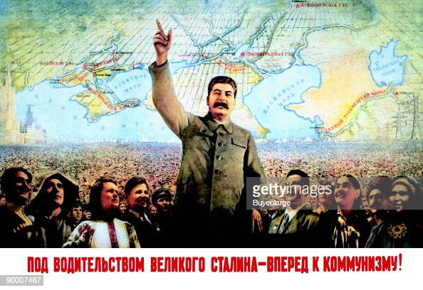 In front of a map of the world Stalin stands with arms raised leading the masses of his people
