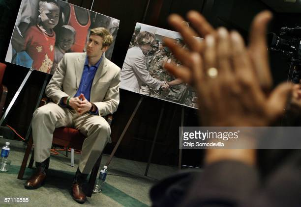 In front of a photograph of children from Darfur Olympic speed skating gold medalist Joey Cheek recieves a round of applause during a news conference...