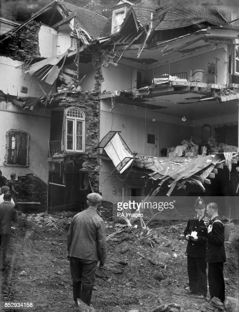 In front of houses wrecked by the floods police use a walkietalkie radio during rescue and salvage work in devastated Lynmouth Devon Throughout the...