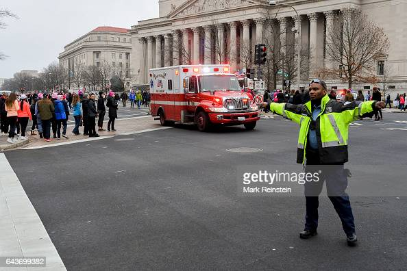 In front of the National Archives Building a police officer directs traffic in the crosswalk of 7th and Pennsylvania Avenue NW as an ambulance passes...