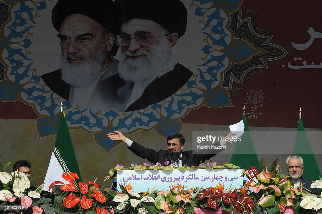 In front of the pictures of <a gi-track='captionPersonalityLinkClicked' href=/galleries/search?phrase=Ayatollah+Khomeini&family=editorial&specificpeople=226737 ng-click='$event.stopPropagation()'>Ayatollah Khomeini</a> (L) and Ayatollah Khamenei, Iranian president <a gi-track='captionPersonalityLinkClicked' href=/galleries/search?phrase=Mahmoud+Ahmadinejad&family=editorial&specificpeople=221337 ng-click='$event.stopPropagation()'>Mahmoud Ahmadinejad</a> greets the crowd at the end of his speech during the 34th anniversary of the Islamic revolution on February 10, 2013 in Tehran, Iran.
