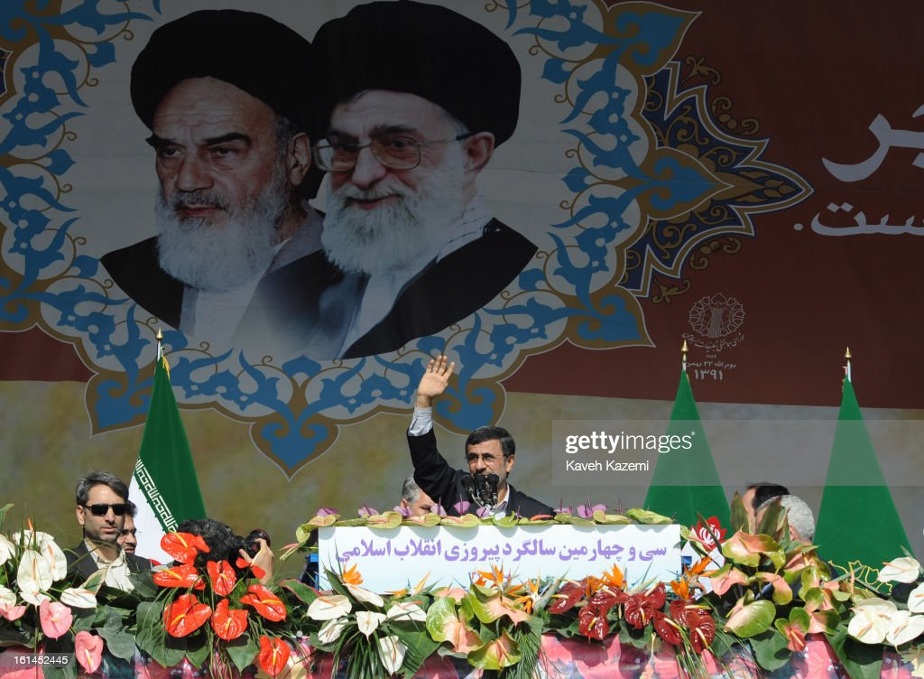 In front of the pictures of <a gi-track='captionPersonalityLinkClicked' href=/galleries/search?phrase=Ayatollah+Khomeini&family=editorial&specificpeople=226737 ng-click='$event.stopPropagation()'>Ayatollah Khomeini</a> (L) and Ayatollah Khamenei, Iranian president Mahmoud Ahmadinejad greets the crowd during the 34th anniversary of the Islamic revolution on February 10, 2013 in Tehran, Iran.