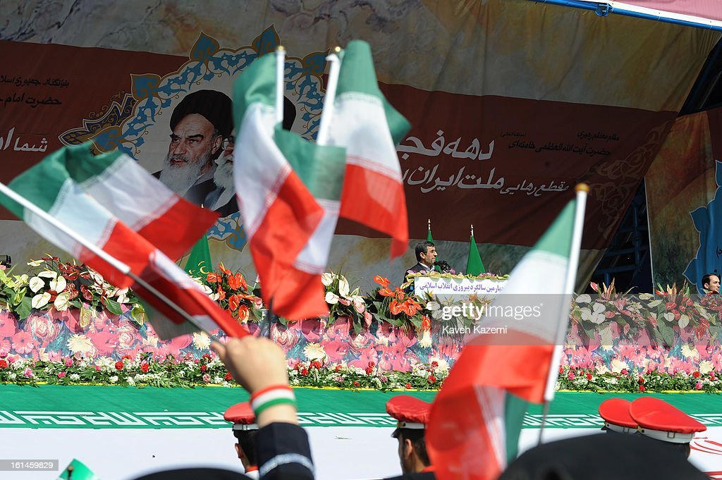 In front of the pictures of <a gi-track='captionPersonalityLinkClicked' href=/galleries/search?phrase=Ayatollah+Khomeini&family=editorial&specificpeople=226737 ng-click='$event.stopPropagation()'>Ayatollah Khomeini</a> (L) and Ayatollah Khamenei, Iranian president <a gi-track='captionPersonalityLinkClicked' href=/galleries/search?phrase=Mahmoud+Ahmadinejad&family=editorial&specificpeople=221337 ng-click='$event.stopPropagation()'>Mahmoud Ahmadinejad</a> greets the crowd during the 34th anniversary of the Islamic revolution on February 10, 2013 in Tehran, Iran.