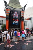 In front of the TCL Chinese Theater people walk on the Hollywood Walk of Fame and the celebrity hand and footprints Los Angeles California July 20...