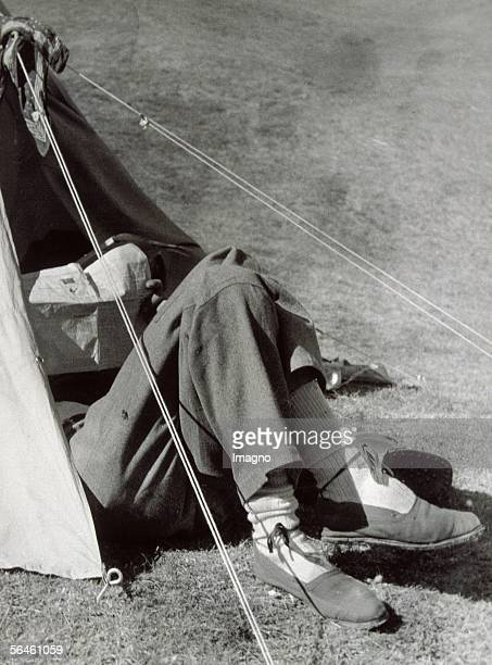 In front of the tent boy with espadrilles is reading a news paper halfway covered by the tent Photography France about 1930 [Vor dem Zelt Junge mit...