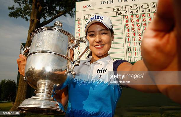In Gee Chun of South Korea poses with the trophy as she takes a simulated 'Selfie' after winning the US Women's Open at Lancaster Country Club on...