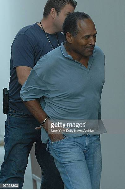 In handcuffs OJ Simpson is transferred by police officers to the Clark County Detention Center in Las Vegas Nev after being arrested in connection...