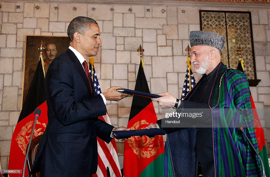 In handout image released by the Afghan Presidents Office, US President <a gi-track='captionPersonalityLinkClicked' href=/galleries/search?phrase=Barack+Obama&family=editorial&specificpeople=203260 ng-click='$event.stopPropagation()'>Barack Obama</a> (L) exchanges documents with Afghanistan President <a gi-track='captionPersonalityLinkClicked' href=/galleries/search?phrase=Hamid+Karzai&family=editorial&specificpeople=121540 ng-click='$event.stopPropagation()'>Hamid Karzai</a> (R), during their meeting on May 2, 2012 in Kabul, Afghanistan. The US and Afghan Presidents signed a long-term strategic partnership outlining their cooperation following the 2014 withdrawal of NATO and allied forces. Obama made the secret visit to the country on the anniversary of Osama Bin Laden's death and made a primetime tv address to the American people from Bagram Air Base in Kabul.