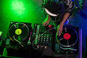 overhead view of professional african american DJ in headphones with sound mixer in nightclub