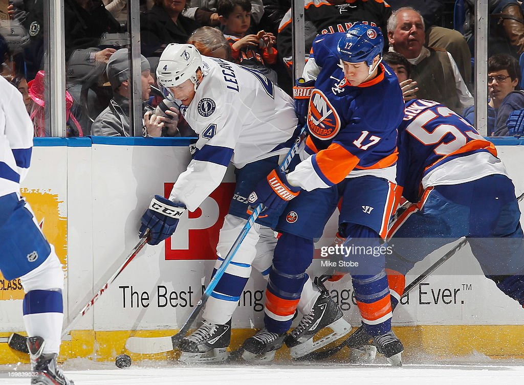 In his 1,000th career game, Vincent Lecavalier #4 of the Tampa Bay Lightning battles for the puck against Matt Martin #17 of the New York Islanders at Nassau Veterans Memorial Coliseum on January 21, 2013 in Uniondale, New York.
