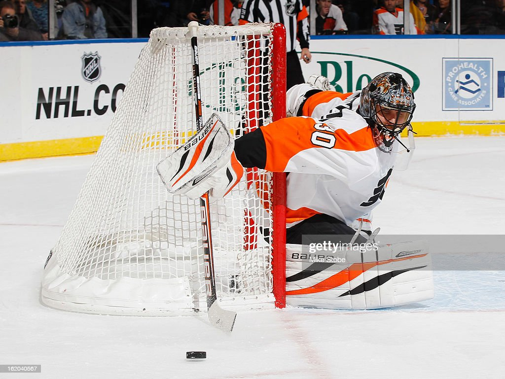 In his 400th NHL game, Ilya Bryzgalov #30 of the Philadelphia Flyers clears the puck away from the net during the game against the New York Islanders at Nassau Veterans Memorial Coliseum on February 18, 2013 in Uniondale, New York.