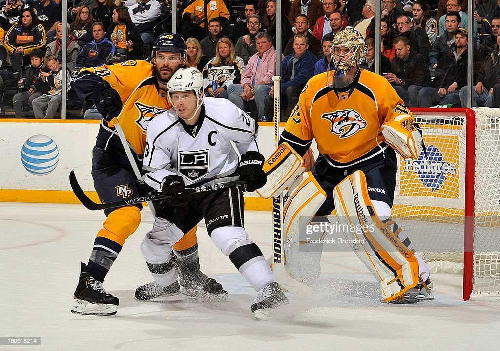 In his 500th career NHL game Paul Gaustad #28 of the Nashville Predators ties up Dustin Brown #23 of the Los Angeles Kings in front of goalie Pekka Rinne #35 at the Bridgestone Arena on February 7, 2013 in Nashville, Tennessee.