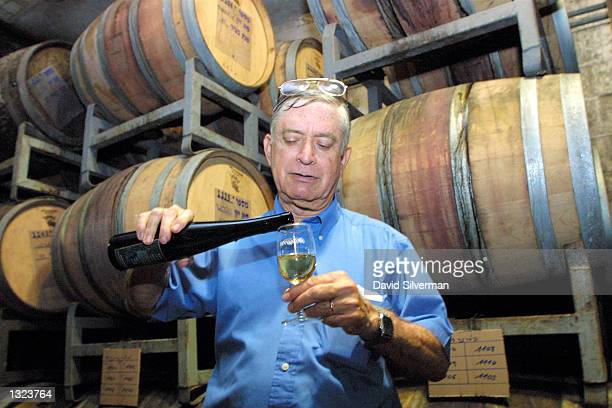 In his cellar at the Binyamina Winery cellar master Amram Surasky pours July 9 a glass of 'healthy white' Muscat developed in cooperation with...