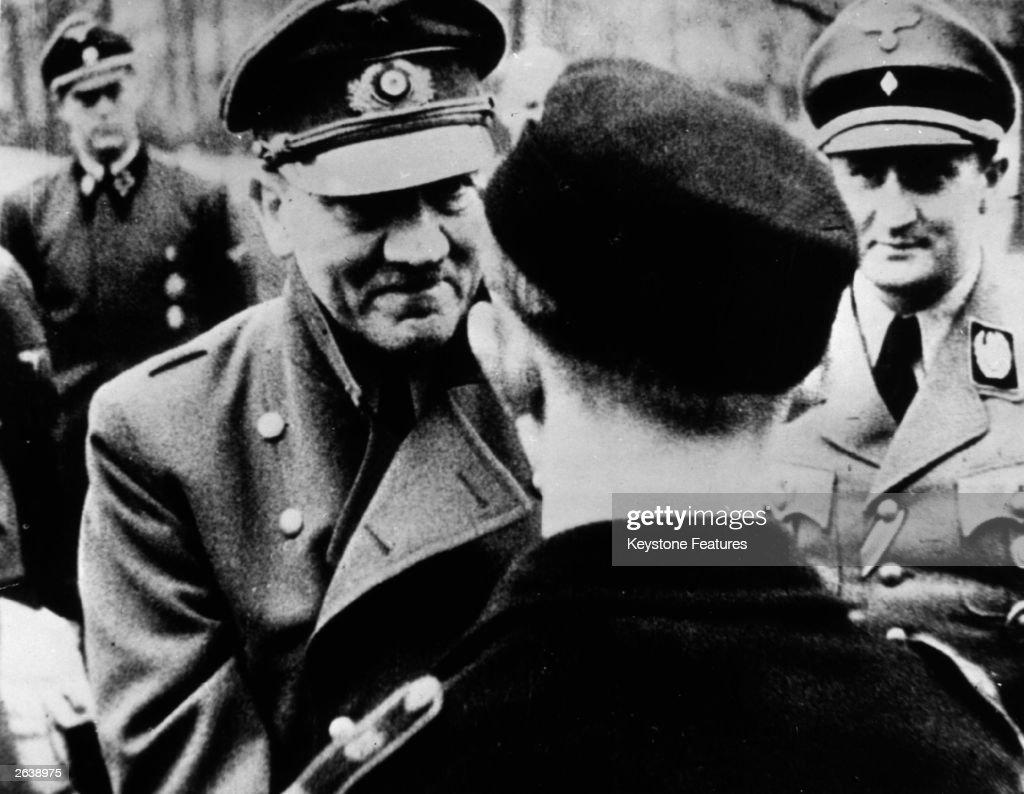 In his last official photo, Adolf Hitler (1889 - 1945) leaves the safety of his bunker to award decorations to members of Hitler Youth.