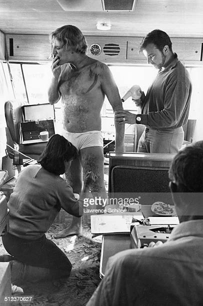 In his trailer Irish actor Richard Harris smokes a cigarette as makeup artists apply mud and 'injuries' to him during production of the film 'A Man...